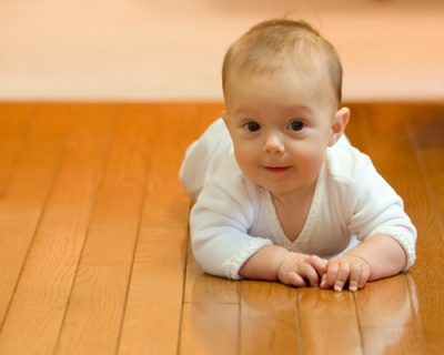Six month old baby girl proud and happy crawling on a wooden floor. Room for text left.